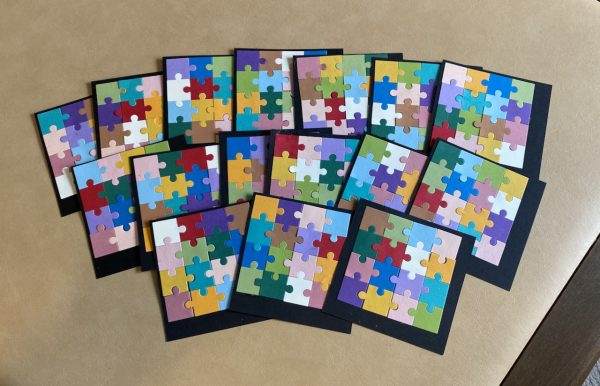 Basic black card stock covered with multi colored puzzle pieces